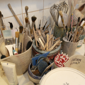 Collection of brushes and pots in ceramics art class